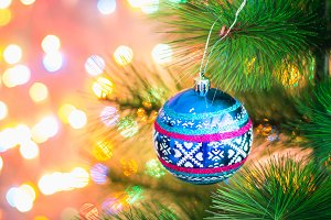Christmas blue ball on a Christmas tree on a background of lights garlands, bokeh.