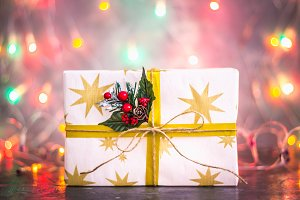A gift for Christmas on the background of lights of garlands, bokeh.