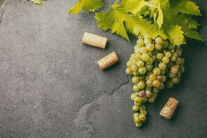 Grape and corkscrews wine concept, Stone background, top view