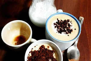 Pitcher with milk, two cappuccino