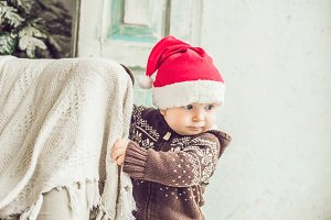 Cute little boy in Santa hat, looking to copy space