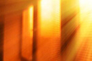 Diagonal venetian blinds with light leak bokeh background