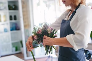 Skillful female florist creating bou