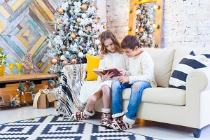 Two children a boy and a girl at a Christmas tree on a sofa with gifts. In light colors. Read the book