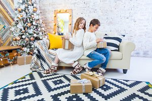 Two children a boy and a girl at a Christmas tree on a sofa with gifts. In light colors. spying on each other's gift