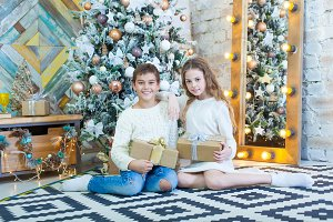 Happy children holding Christmas gifts and sitting on the floor