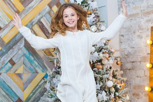 Christmas. Beautiful smiling girl. Over christmas tree lights background. happy new year. jumps