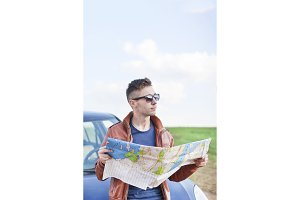 Young man reading road map