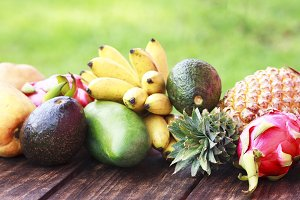Mixed exotic fruits on wood background. Healthy eating, dieting. Top view with grass copy space