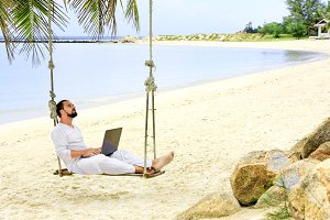 Man working with a laptop, on a hammock in the beach. Show win