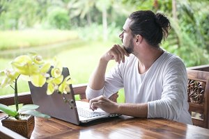 Freelance work on laptop. Man sitting at wooden desk inside garden working on computer