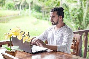 Freelance work on laptop. Man sitting at wooden desk inside garden working on computer