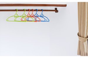 Nothing To Wear Design Sale Concept Coat Hanger on White Wall Copy Space
