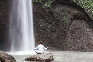 Man sitting in meditation yoga on rock at waterfall Tibumana
