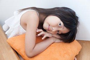 Girl sitting hugging pillow orange.