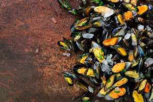 Mussels, molluscs, seaweed, sea plants, ice on old vintage rustic metal background. Top view, copy space