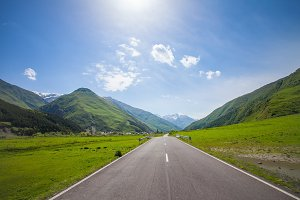 Mountain empty road, green hills, blue sunny sky