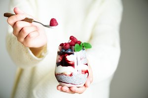 Girl in white sweater holds glass with chia milk dessert, raspberries, blueberries, mint. Healthy breakfast concept. Copy space, close up
