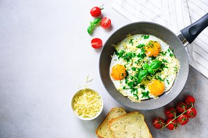 Fried eggs in pan, herbs, spices, cherry tomatoes, cheese toasts, basil for breakfast on grey concrete stone background. Copy space, top view, flat lay
