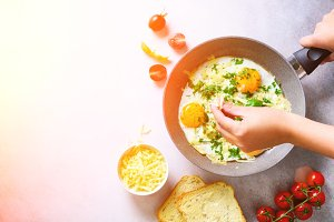 Sunny morning. Breakfast with fried eggs in pan, herbs, spices, cherry tomatoes, cheese toasts, basil on grey concrete stone background. Copy space, top view, flat lay, sunlights