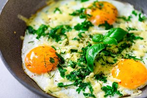 Three fried eggs with peppers, herbs, cheese in pan, closeup, macro