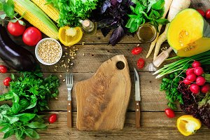 Vegetables on wooden background. Herbs, basil, onion, pumpkin, pine nuts, tomatoes, corn, radish, eggplant, bell pepper, salt, spices, oil, spinach, parsley, lettuce leaves. Top view, copy space