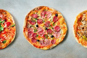 Pizza pattern. Three pieces set on grey concrete background. Top view, copyspace