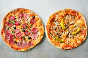 Fresh italian pizza with mushrooms, ham, tomatoes, cheese, olive, pepper on grey concrete background. Copy space. Top view.
