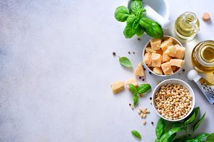 Ingredients for homemade pesto - basil, lemon, parmesan, pine nuts, garlic, olive oil and salt on white concrete background. Top view, flat lay, copyspace. Banner