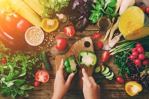 Woman hands cutting vegetables on wooden background. Vegetables cooking ingredients, top view, copy space, flat lay. Sunlight bokeh