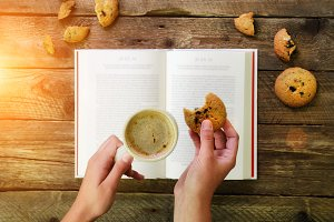 Сoffee cup, opened book, alarm clock, cookie on wooden rustic vintage background. Top view, copy space. Sunny morning