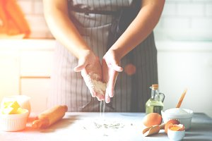 Female hands kneading dough, baking background. Cooking ingredients - eggs, flour, sugar, butter, milk, rolling pin on white style kitchen. Copy space
