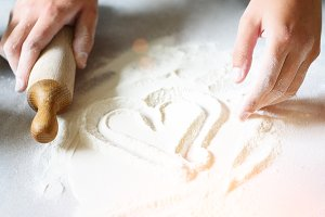 Heart of flour. Baking background with rolling pin, eggs, milk, butter on white kitchen table. Valentines day cooking, love concept.