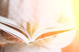 Book with opened pages and shape of heart in girl hands. Copy space. Love concept. Festive background with bokeh and sunlight. Magic fairy tale