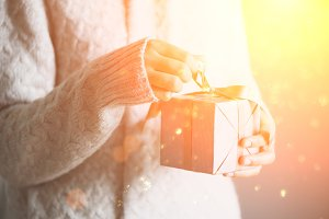 Female hands holding gift box. Copy space. Christmas, hew year, birthday concept. Festive background with bokeh and sunlight. Magic fairy tale