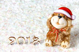 Wooden figures of 2018 on snow. Christmas atmosphere. The new year 2018. A toy dog is a symbol of the New Year.