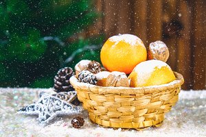 Mandarins, walnuts and bumps in a basket on the background of a Christmas tree.