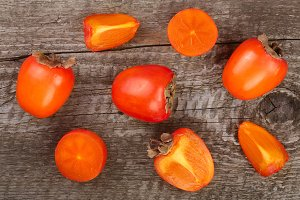 persimmon on old wooden background. Top view. Flat lay pattern