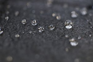 Little water drops on black leather