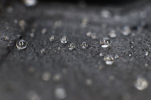 Small water drops on black leather