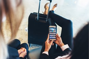 Close-up view of female holding smartphone with different applications on screen sitting with her legs resting on her suitcase