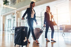 Two stylish female travelers walking with their luggage in airport