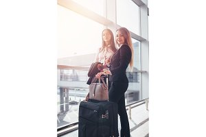 Two young businesswomen standing near window holding their suitcases waiting for the flight in airport