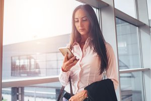 Portrait of young businesswoman using smartphone while walking to boarding area in airport