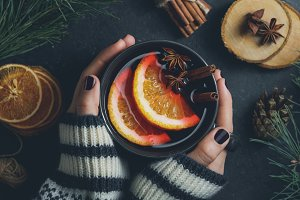 Hands holding a mug with mulled wine