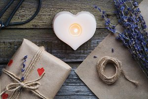 Top view of the gift in a kraft paper, the bouquet with lavender and the candle in shape of heart on the old wooden background. Copy space.