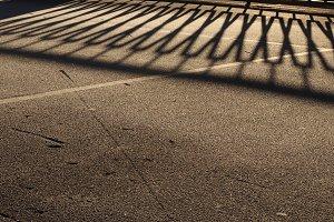 Guardrail Shadow on Icy Asphalt Road