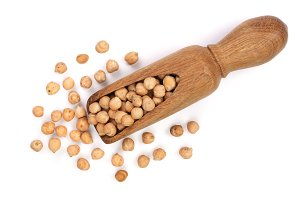 Dry raw organic chickpeas in a wooden scoop isolated on white background. Top view
