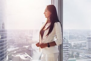 Portrait of pensive successful young woman boss standing near the window in office looking at cityscape