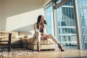 Attractive businesswoman wearing formal office clothing sitting in seductive posture on a sofa at modern apartment